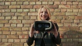 Una chica joven elegante cerca de una pared de ladrillo trae los vidrios virtuales a la cámara metrajes