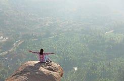 Una chica joven en una actitud del loto está saludando el sol en un fondo imagenes de archivo