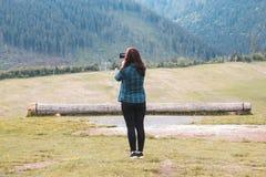 Una chica joven en una camisa del verde azul se coloca en un prado y toma imagen de archivo libre de regalías