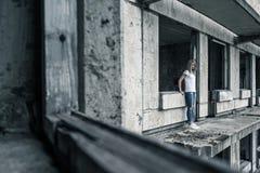 Una chica joven en una camiseta blanca y tejanos se está colocando al borde de un balcón arruinado en un edificio arruinado tempr Imágenes de archivo libres de regalías