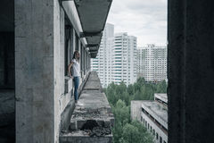 Una chica joven en una camiseta blanca y tejanos se está colocando al borde de un balcón arruinado en un edificio arruinado tempr Imagen de archivo
