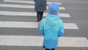 Una chica joven en una chaqueta azul cruza el camino a través de una cebra Encrucijada en la ciudad metrajes