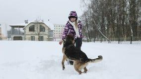 Una chica joven en una chaqueta del invierno juega con un pastor alemán hermoso en la nieve almacen de video