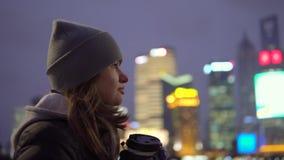 Una chica joven en una chaqueta negra y paseos del sombrero alrededor de la Shangai hermosa con café en sus manos almacen de metraje de vídeo