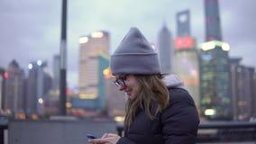 Una chica joven en una chaqueta y un sombrero negros camina y reescribe lentamente por el teléfono metrajes