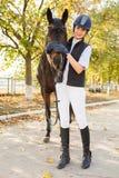 Una chica joven en crecimiento completo en un parque del otoño abrazó la cara del ` s del caballo con sus manos Imagen de archivo