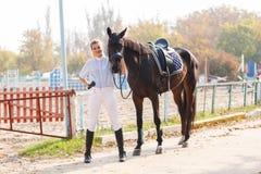 Una chica joven en el equipo del montar a caballo se coloca cerca de caballo oscuro outdoors Imagen de archivo