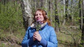 Una chica joven en el parque, auriculares que llevan a escuchar la música Mujer que disfruta de música en auriculares metrajes