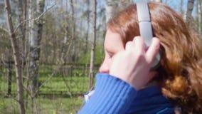 Una chica joven en el parque lleva los auriculares para escuchar la música Una mujer entra para los deportes y disfruta de música almacen de video
