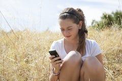 Una chica joven en el teléfono Fotografía de archivo
