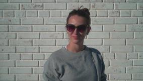 Una chica joven en gafas de sol está mirando en la cámara y está sonriendo contra una pared de ladrillo blanca Muchacha que come  metrajes