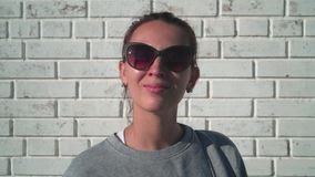 Una chica joven en gafas de sol está mirando en la cámara y está sonriendo contra una pared de ladrillo blanca Muchacha que come  almacen de metraje de vídeo