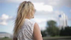 Una chica joven en gafas de sol que disfruta de un día de verano almacen de metraje de vídeo