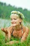 Una chica joven en una guirnalda de manzanillas miente en un prado verde Cara hermosa soñadora imagen de archivo