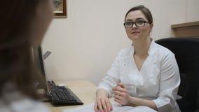 Una chica joven en la cita de un doctor El doctor prescribe el tratamiento al paciente almacen de video