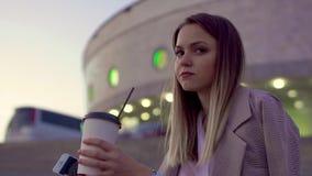 Una chica joven en la ciudad de igualación, sosteniendo el café y el teléfono, esperando una reunión, congelado, lanzó en su chaq almacen de metraje de vídeo