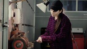 Una chica joven en la máquina de pulir afila la herramienta almacen de video