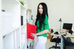 Una chica joven en la oficina saca carpetas con los documentos Fotos de archivo libres de regalías