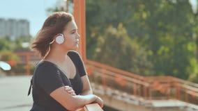 Una chica joven en los auriculares blancos con placer escucha la música en una tarde caliente del verano almacen de video