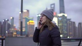 Una chica joven en paseos lentos de una chaqueta negra y del sombrero mientras que habla en el teléfono almacen de metraje de vídeo