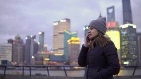 Una chica joven en paseos lentos de una chaqueta negra y del sombrero mientras que habla en el teléfono almacen de video