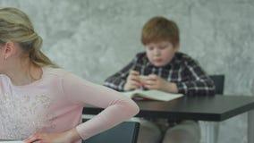 Una chica joven en una sala de clase que concentra en su prueba, mientras que su compañero de clase que juega a juegos en smartph metrajes