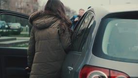 Una chica joven en tiempo del otoño sube a su coche y consigue detrás de la rueda almacen de metraje de vídeo