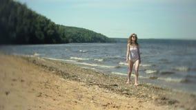Una chica joven en un bikini blanco camina a lo largo de la orilla almacen de metraje de vídeo