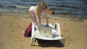 Una chica joven en un bikini blanco camina a lo largo de la orilla almacen de video