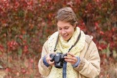 Una chica joven en un bosque del otoño con una cámara Foto de archivo libre de regalías