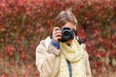 Una chica joven en un bosque del otoño con una cámara Fotos de archivo