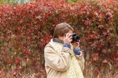 Una chica joven en un bosque del otoño con una cámara Fotos de archivo libres de regalías