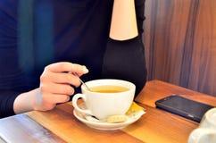 Una chica joven en un café está bebiendo té imagen de archivo