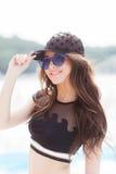 Una chica joven en un casquillo negro, un bañador negro y gafas de sol azules se coloca en el fondo de la playa, mira Fotografía de archivo