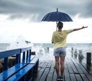 Una chica joven en un embarcadero con un paraguas Foto de archivo