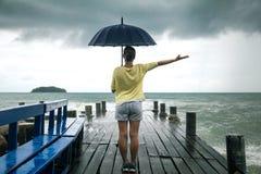 Una chica joven en un embarcadero con un paraguas Imagen de archivo