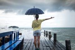 Una chica joven en un embarcadero con un paraguas Fotografía de archivo