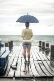 Una chica joven en un embarcadero con un paraguas Fotos de archivo libres de regalías