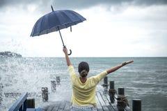 Una chica joven en un embarcadero con un paraguas Imagenes de archivo