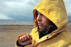 Una chica joven en un impermeable amarillo mojado mira el agua de la bahía, nubes oscuras de arriba y llueve, un triste y Fotos de archivo