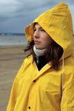 Una chica joven en un impermeable amarillo mojado mira el agua del Foto de archivo libre de regalías