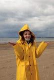 Una chica joven en un impermeable amarillo se está colocando en la lluvia en la orilla de la bahía, nubes oscuras con lluvia, man Imagenes de archivo