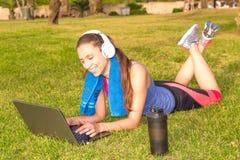 Una chica joven en un parque en la hierba después del entrenamiento de la aptitud con el ordenador portátil y los auriculares Foto de archivo
