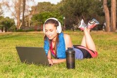 Una chica joven en un parque en la hierba después del entrenamiento de la aptitud con el ordenador portátil y los auriculares Foto de archivo libre de regalías