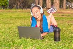 Una chica joven en un parque en la hierba después del entrenamiento de la aptitud con el ordenador portátil y los auriculares Fotografía de archivo
