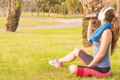 Una chica joven en un parque en la hierba después del entrenamiento de la aptitud con los auriculares y ella bebe sacudida de la  Fotografía de archivo