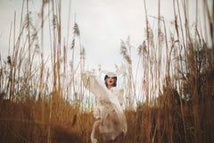 Una chica joven en un sombrero elegante y un vestido blanco que camina en un campo de trigo foto de archivo libre de regalías