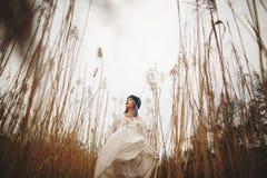 Una chica joven en un sombrero elegante y un vestido blanco que camina en un campo de trigo imagen de archivo