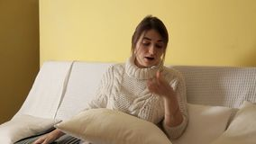 Una chica joven en un suéter caliente acogedor en un invierno que iguala en casa, leyendo un libro y caer dormidos almacen de metraje de vídeo