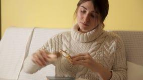 Una chica joven en un suéter caliente acogedor en un invierno que iguala en casa, los vidrios, leyendo un libro y caer dormidos C almacen de metraje de vídeo